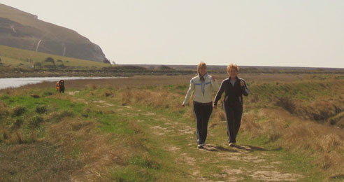Two women walking past a river and cliff outside in the sun