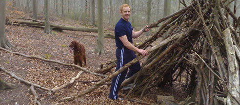 A picture of a man building a wooden wigwam