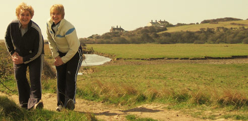 Two lady's stretching thier hamstrings at Cuckmere Haven